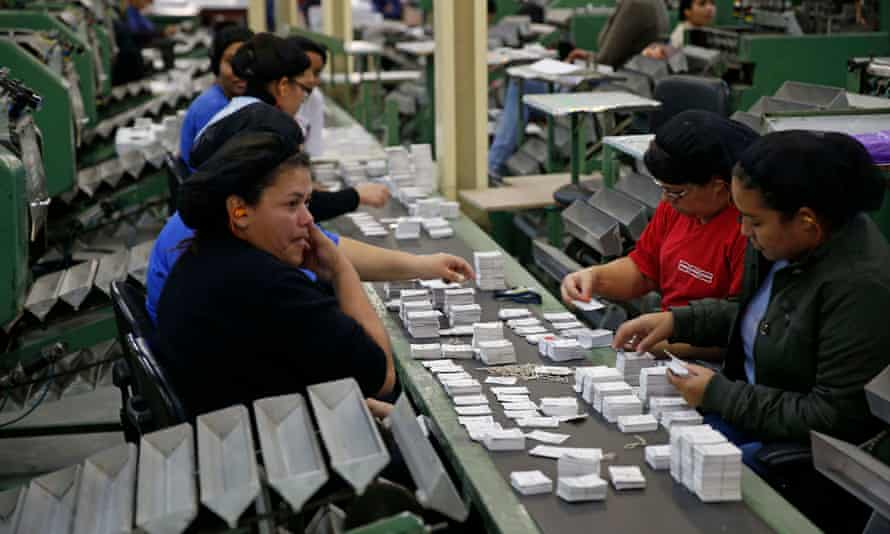 Workers sort stickers into piles at the Panini factory outside São Paolo for the 2014 World Cup collection