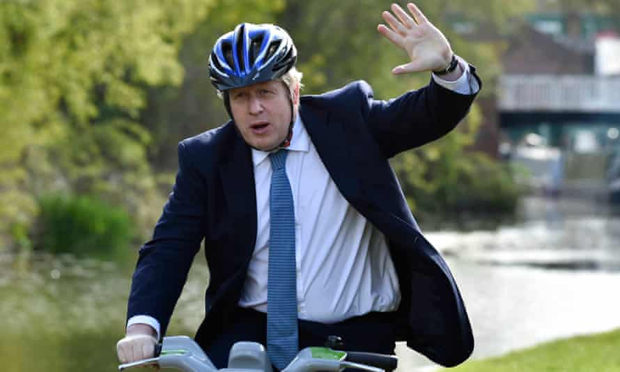 Boris Johnson waves as he rides a bike ride along the towpath of the Stourbridge canal in the West Midlands