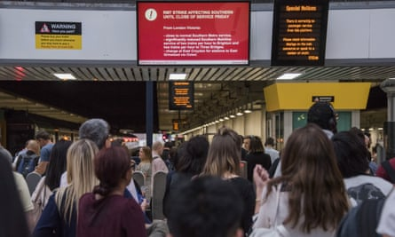 Commuters wait under the strike information screen at Victoria station in London.