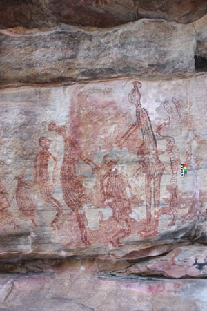 A painting from Namunidjbuk shows two male Maliwawas with ball headdresses reaching down to a shorter human figure with a snake behind the male on the right and behind the left male a female and a macropod. A human figure with a cone and feather headdress is above.