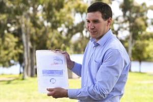 Liberal leader Alistair Coe holds a frozen rates bill during a press conference on Friday