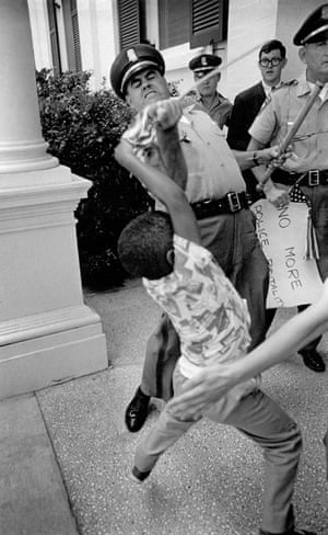 A Mississippi highway patrolman, Hughie Kohler, wrestles with five-year-old Anthony Quin on 17 June 1965, grabbing his small US flag before arresting him and his mother. They had wanted to protest against the election of congressmen from districts where black people were not allowed to vote