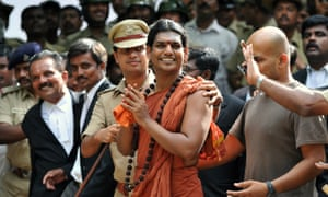 Hindu 'godman' Nithyananda, being escorted by police from a court hearing
