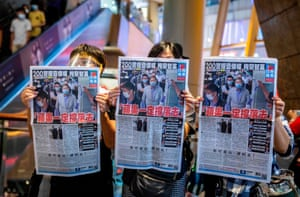 People hold up copies of the Apple Daily as they protest for press freedom inside a mall in Hong Kong on August 11, 2020.