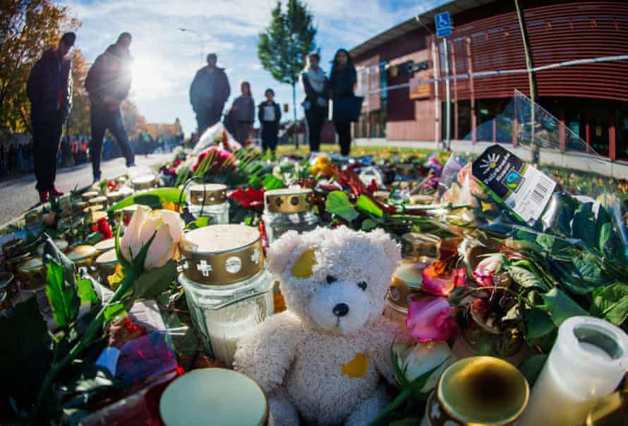 People stand by candles and flowers outside the Kronan school in Trollhättan.