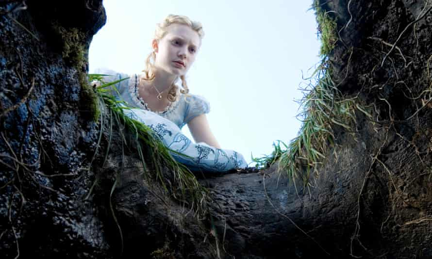 Mia Wasikowska as Alice peering into the rabbit hole in Alice in Wonderland.