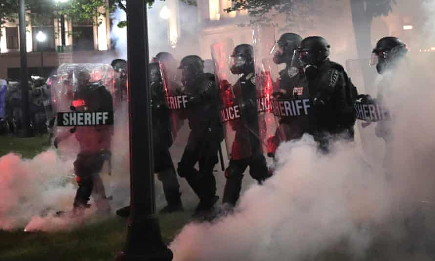 Police try to push back demonstrators near the Kenosha county courthouse during a third night of unrest