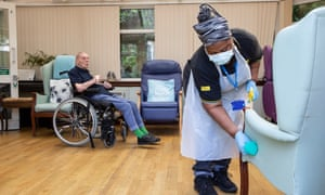 A resident sitting in the lounge at a care home watching a member of staff cleaning an armchair