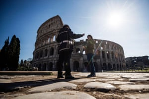 A municipal police officer speaks to a tourist outside the Colosseum in Rome