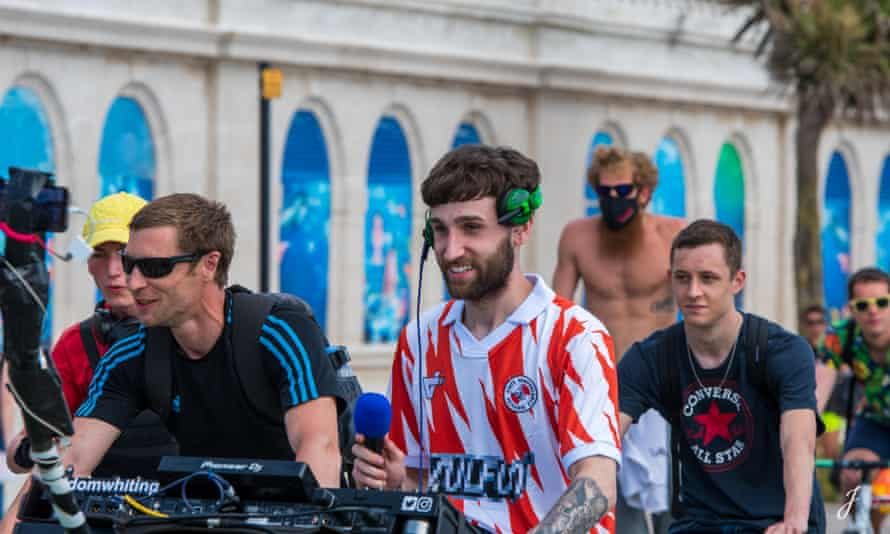 Dom Whiting (centre) leads a procession of cyclists through Brighton to the beat of his drum'n'bass set