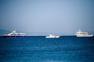 A coastguard boat escorts two small Turkish ferries as they arrive in Dikili