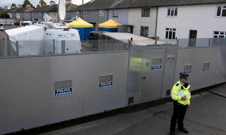 A police officer stands by a barrier cordon outside an address in Sunbury-on-Thames, London.