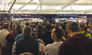 Passengers wait at passport control at Stansted airport.