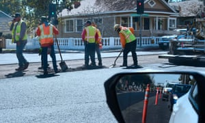 Workers repave a road