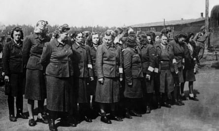 Surrendered SS guards from Bergen-Belsen are watched by Allied soldiers.