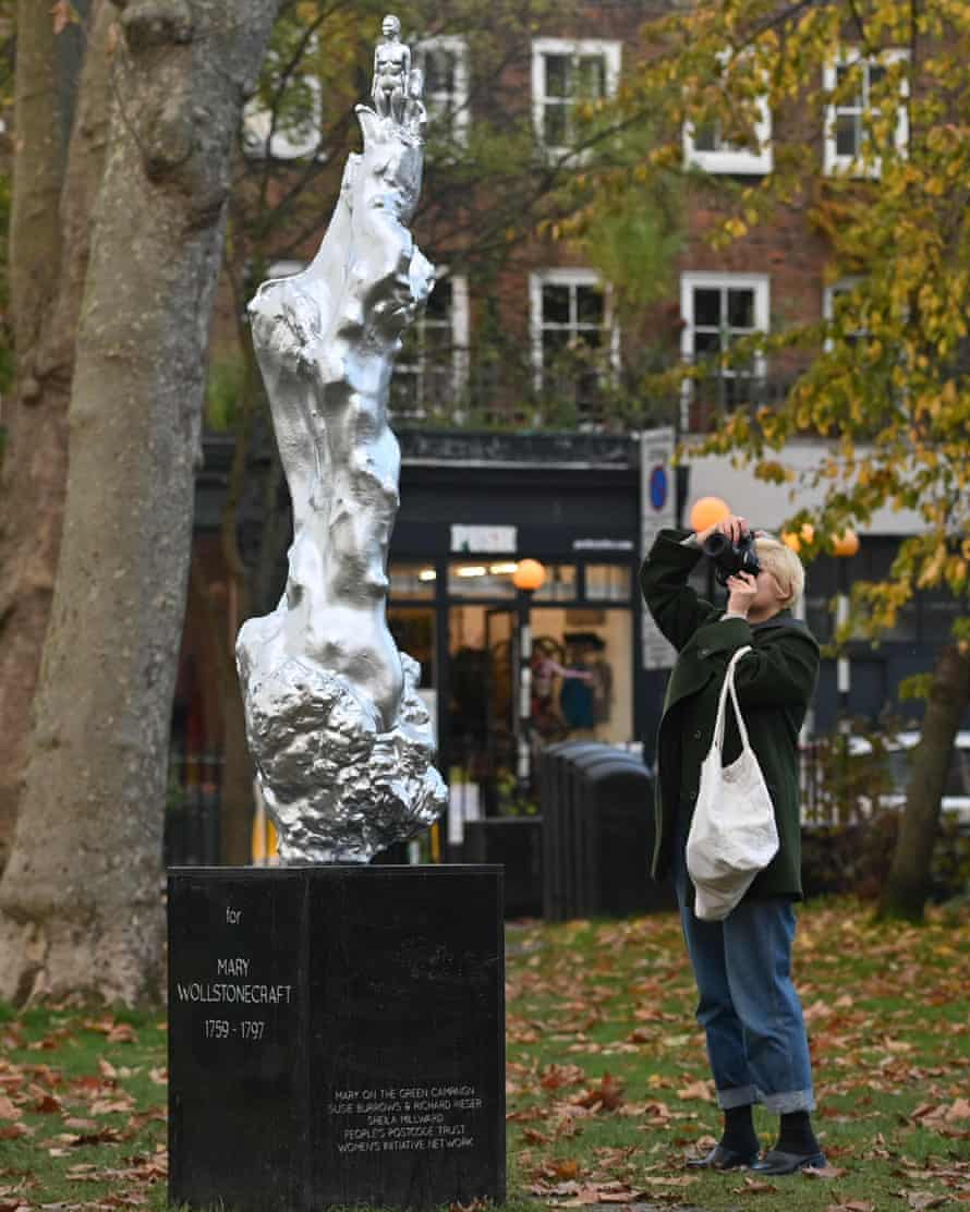 A woman photographs the new sculpture of British author and feminist icon Mary Wollstonecraft.