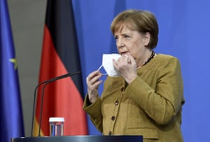 German chancellor Angela Merkel takes off her mask as she arrives to hold a news conference following a virtual summit meeting with G7 leaders at the Chancellery in Berlin, Germany, 19 February 2021.