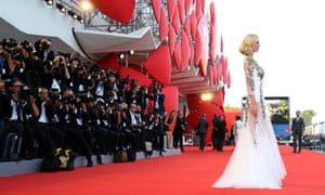 A woman in a white a silver dress stands on the red carpet, surrounded by photographers