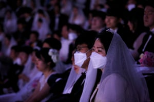 Brides and grooms in audience wearing face masks