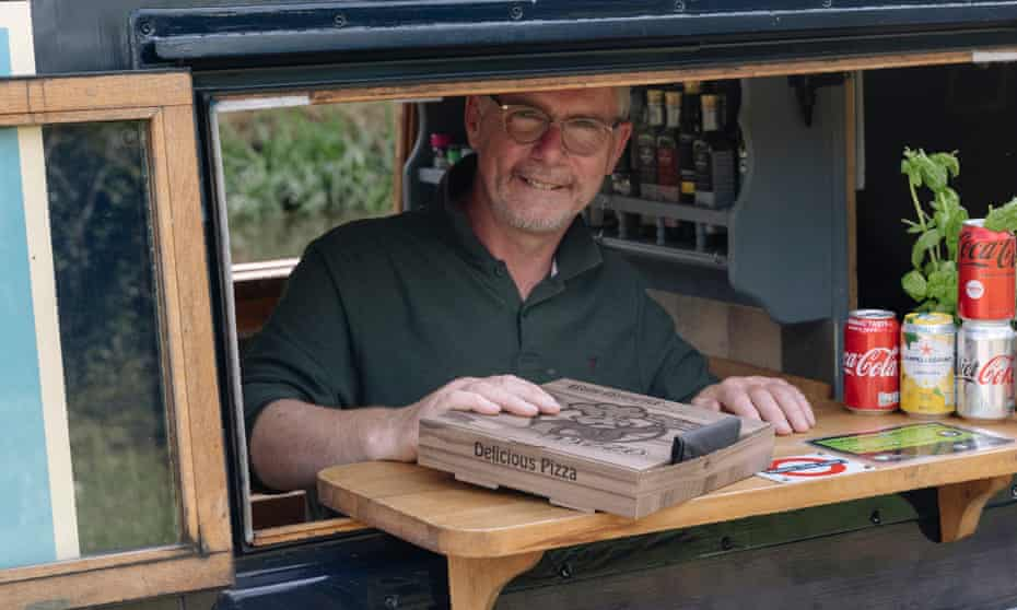Paul Partridge, smiling and passing a pizza in a box through the hatch of his narrowboat