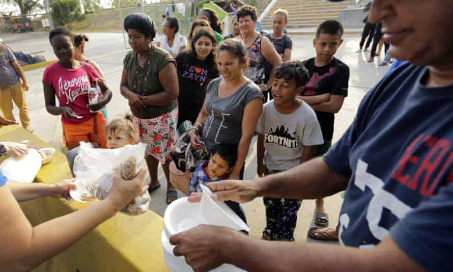 Migrants seeking asylum in the United States receive breakfast from a group of volunteers in near the international bridge in Matamoros, Mexico, on Tuesday.