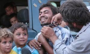 A Manbij man having his beard cut off, August 2016