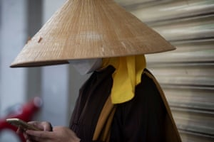A monk wearing a protective mask uses his mobile phone in Ho Chi Minh City.