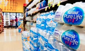 A woman walks past an aisle with bottled water at a supermarket in Los Angeles.