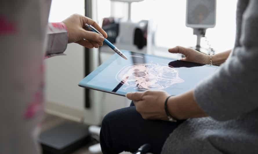 A doctor explaining a digital brain scan to a patient in a clinic