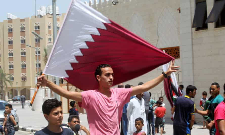 Residents of a Qatari-funded housing project in Gaza wave the emirate's flag at rally
