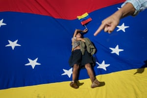 A man points at Oliver Duque, a homeless boy resting on top of a Venezuelan national flag during a demonstration called by opposition politician Juan Guaido, who's urging masses into the streets to force President Nicolás Maduro from power, in Maracaibo, Venezuela, Saturday, Nov. 16, 2019.
