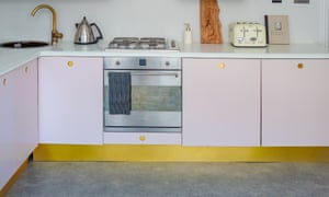 The refurbished galley kitchen in soft pink with brass fittings.