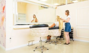 Fitness instructor Anna having hair extensions fitted by a salon employee, also called Anna.