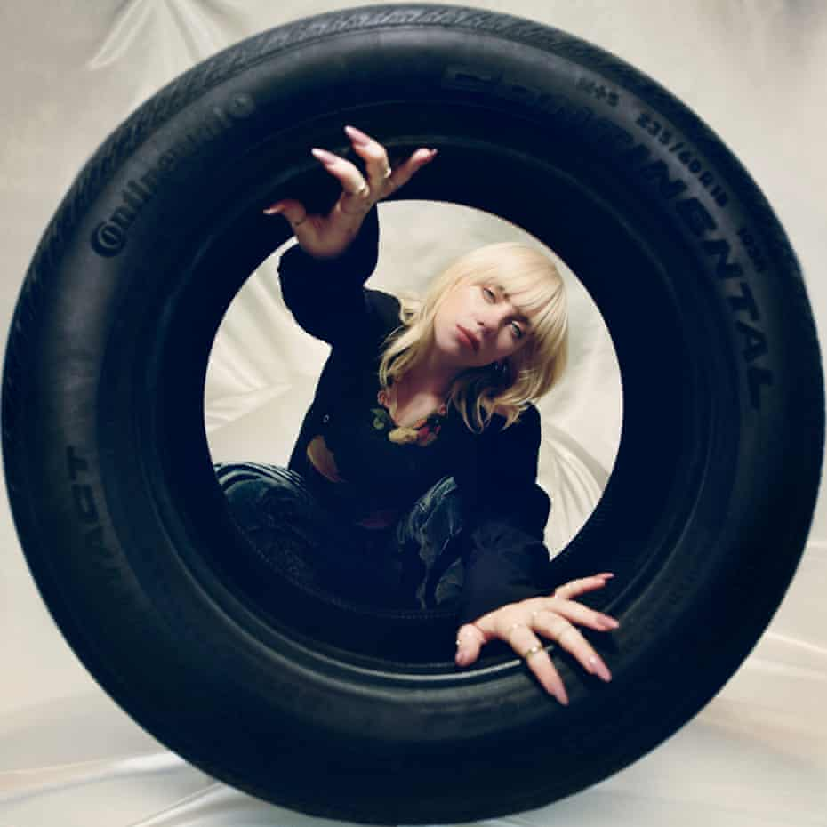 Billie Eilish looking through a tyre