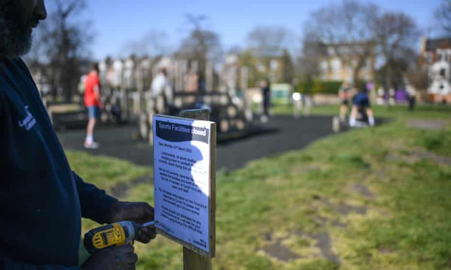 A council worker puts up a sign notifying the closure of an outdoor gym on Clapham Common in London.