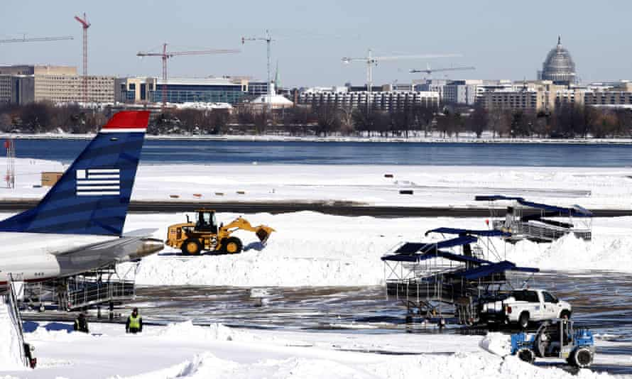 Workers clear snow on the tarmac at Ronald Reagan national airport, Washington DC, following the blizzard.