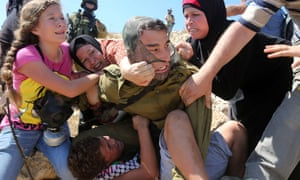Tamimi family members try to pull the Israeli soldier off Mohammed, 11, during protests against Palestinian land confiscation in Nabi Saleh, West Bank.