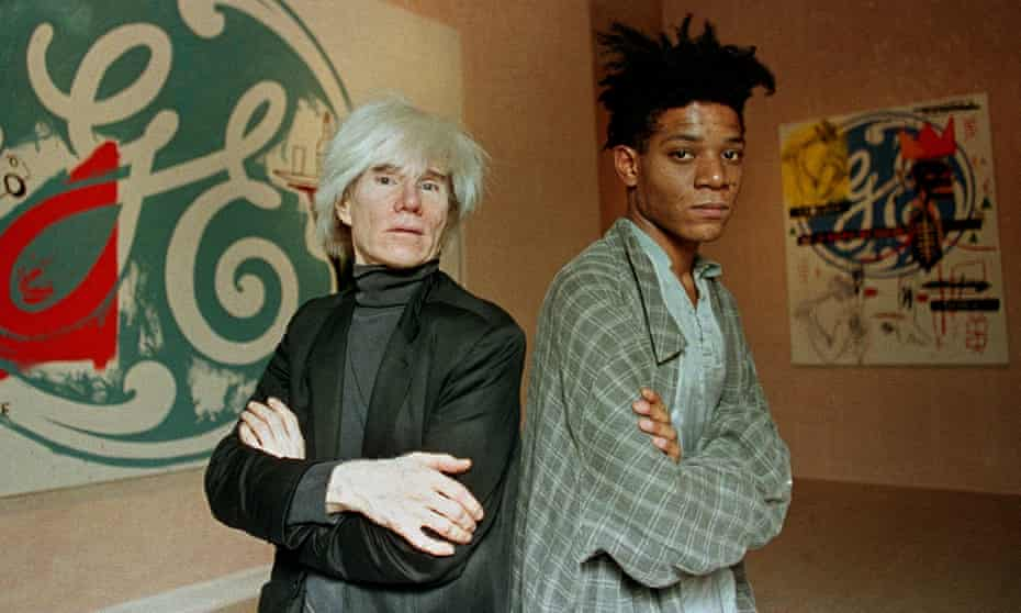 Pop artists Andy Warhol, left, and Jean-Michel Basquiat pose in front of their collaborative paintings on display at the Tony Shafrazi Gallery in New York, 1985
