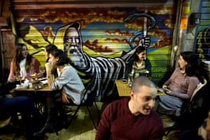 Israelis sit in a cafe bar in front of a depiction of Moses