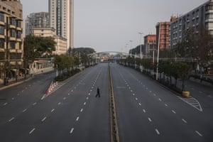 A man crosses an empty highway