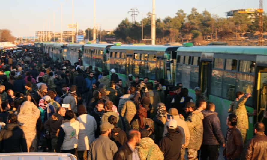 Residents gathering near green government buses for evacuation on Thursday.