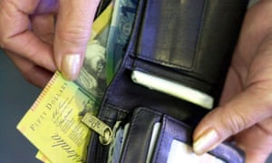 A hand placing Australian notes into a wallet