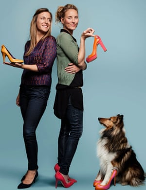 Natalie Dean and Heather Whittle standing back to back and holding a shoe each, a collie dog sitting, looking up at them and with his paws in stiletto shoes