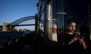 A commuter uses her mobile phone as a Circular Quay to Cockatoo Island ferry passes under the Sydney Harbour Bridge