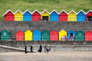 July 2020: a family enjoy a day at the seaside in front of a row of colourful beach huts in Whitby