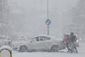 People help push a car that got stuck in the snow in Rochester