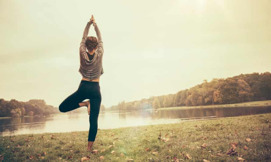 A woman holds a yoga pose as she practises outdoors