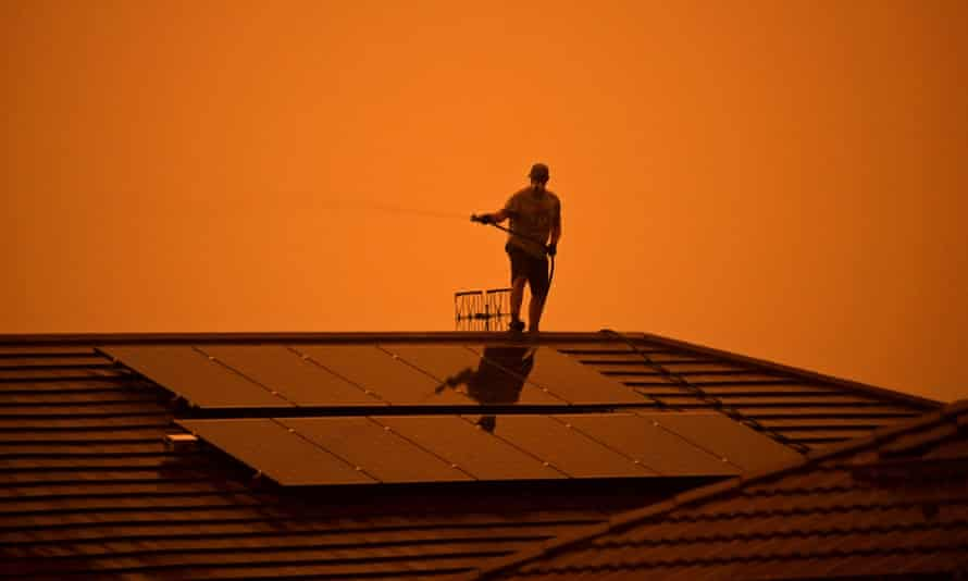 Man hosing his roof against an orange sky