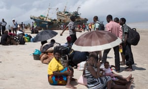 On a beach in Beira, relatives wait for boats to take them to Buzi to search for their loved ones.