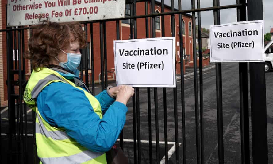 A volunteer puts up signs outside a mobile vaccination clinic in Blackburn, north-west England